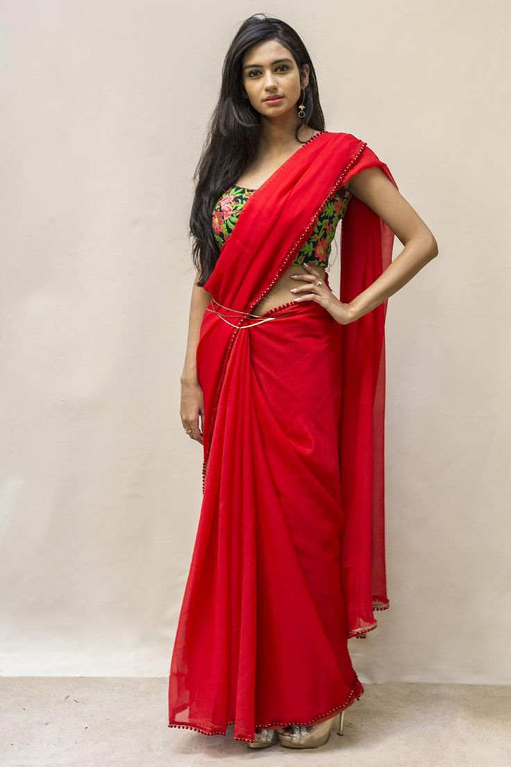 Red as in roses, romance and passion! Loved by poets and warriors alike. A big hand to this soft pure chiffon drape in red, delicately edged with red pom pom's and a surprise pallu detail in an appliqué  of roses. Go ahead…own yourself in this red red drape.Sizzle away in a floral detailed blouse. Or flip things around a bit in golden sheer blouse to yet radiate that charm! #houseofblouse #saree #blouse #indianwear #india #fashion #bollywood #red #chiffon .