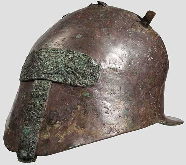 Apulian-Corinthian helmet, 6th/5th century B.C. Hemispherical skull, minimally contoured. The face cutout was closed in ancient times by two riveted, richly decorated, bronze sheets (different alloy, with green corrosion), their palmette decorations have been made more visible in places by modern white ink. Wide flaring neck guard. Remnants of a riveted grest fork. A hole on each side for attaching the chinstraps, 17.5 cm high. Private collection, from Hermann Historica auction