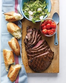 Bistro flavors meet classic steak house in this simple, satisfying meal. The marinade for the flank steak is made with red-wine vinegar, rosemary, and garlic. Serve with smashed and seasoned cherry tomatoes and a salad of crunchy, cold radishes, red onion, and greens. Use a fresh, crusty baguette to sop up the juices or to make sandwiches.
