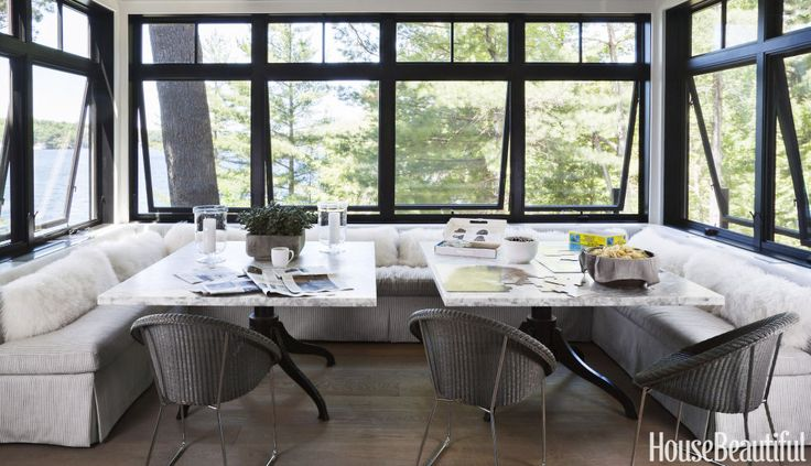 The breakfast nook's awning windows can be cranked open to let in breezes. A pair of marble-topped tables allow easier access to the U-shaped banquette.