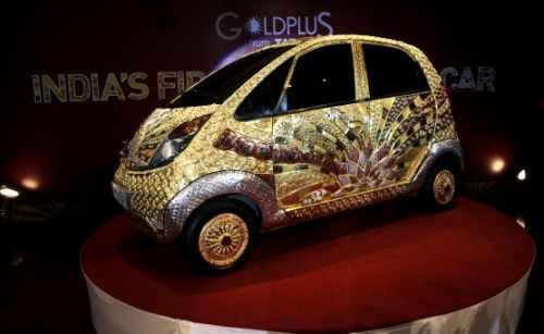 The Tata Motors 'Nano' car crafted in gold, silver and gem stones during its unveiling in Mumbai, India, Monday ,Sept. 19, 2011. This version of the compact car, which was launched two years ago as the world's cheapest car in its original form, is claimed to be first gold jewelry car and made from 80 kilograms of 22 karat gold, 15 kilograms of silver, and numerous gemstones. (AP Photo/Rajanish Kakade)