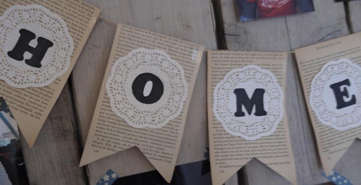 Slinger home, gemaakt van pagina's uit een boek, doilies en letters