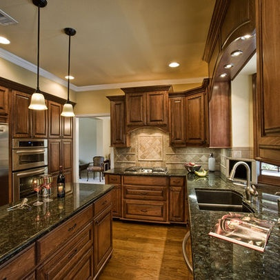 Different  colored wood on floor from that of the cabinet with black pearl countertops!
