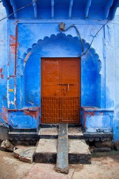 Rustic Red Door With Crowned Arch on Blue Wall House, Jodpur, Rajasthan, India  by Myles Kwesi Hutchful