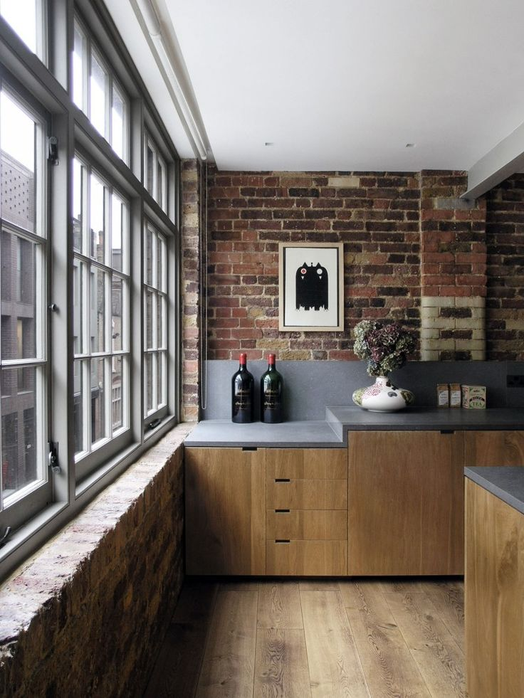 Solid wood kitchen cabinets_gray counters_brick wall_no uppers_wide plank wood floors_McLaren.Excell