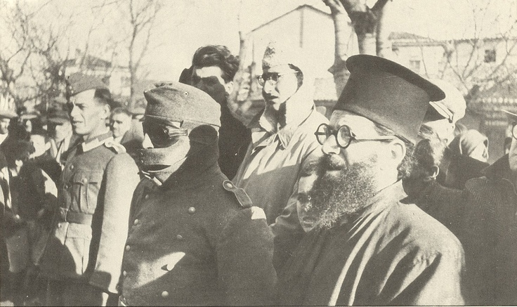 "Greece, 1941-1944. A Greek collaborationist, masked, on the right hand of the orthodox priest, prepares to identify enemies of the Nazi ""New Order"" among his fellow Greeks."