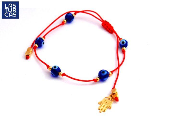 Esta Turca está elaborada en hijo rojo con nudo corredizo, ojos de vidrio fundido, balines y mano hamsa en baño de oro, también disponible en tobillera. Diseño de Mapi, pídela como MPJ14.