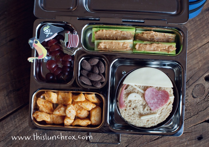 """So today I made a """"pirate lunch"""" including a pirate sandwich with a heart shaped eye patch, celery and peanut butter (use sunbutter if peanut allergies are a concern), grapes, taco flavored Ellsworth cheese curds, almonds packed in a Planet Lunch Box"""