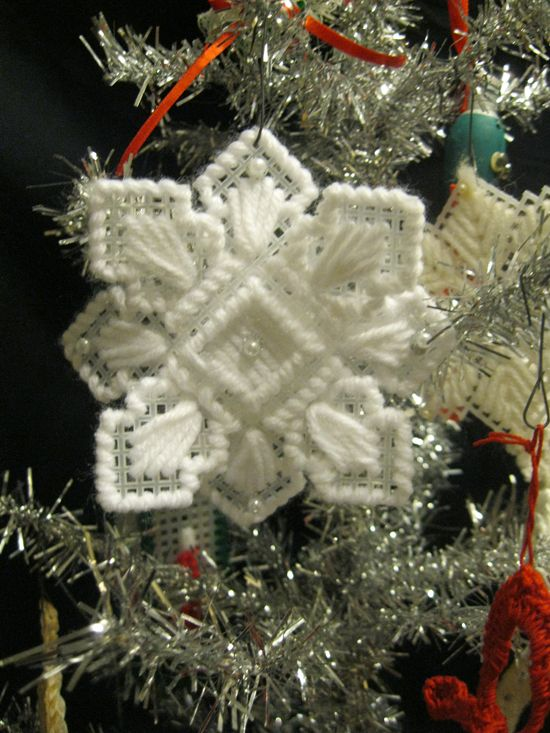 Supplies:        Plastic mesh canvas (one sheet will make six completed ornaments)      White yarn      Pearl beads      Glitter fabric paint      Yarn needle      Scissors    Instructions: