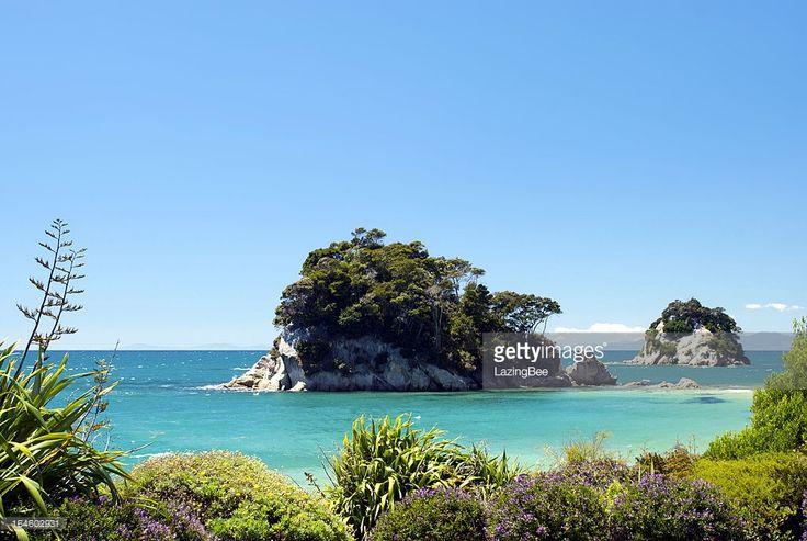 Looking across Little Kaiteriteri Beach's still waters to Torlesse Rock, Kaiteriteri, Tasman Region, New Zealand.