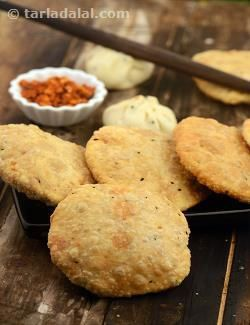 """These puris have a hint of some unusual flavours like urad dal, fennel seeds and kalonji. Traditionally served with """"sookha aloo"""" (a dry potato preparation) for breakfast, they can also be served as part of a main meal."""