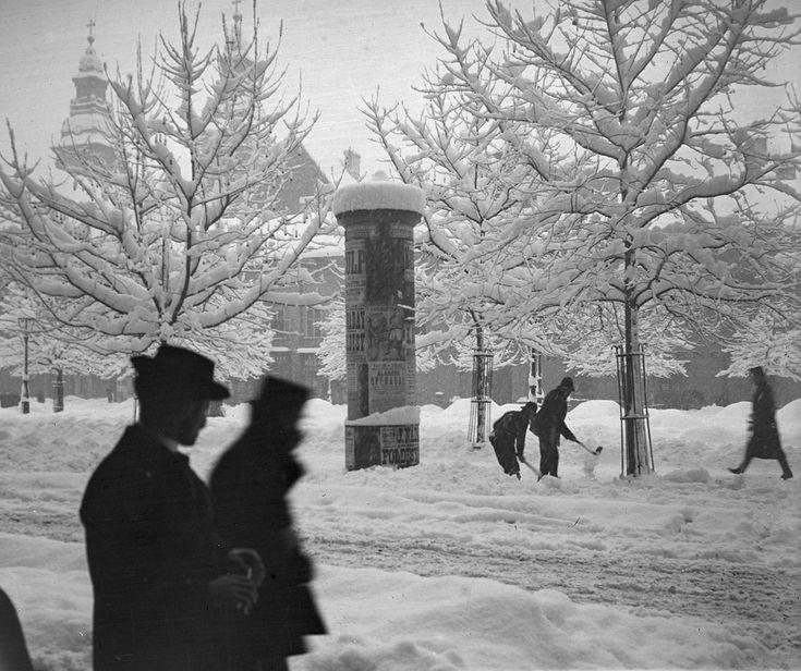 1878-ban merült föl először az ötlet, majd hosszú vacillálás után végül tíz évvel később kerültek helyükre az első hirdetőoszlopok. Ezen az 1907-es képen épp a havat lapátolják az egyik mellett, a háttérben a a Belvárosi Nagyboldogasszony Főplébánia (ma már ebből az irányból nem látszik a piaristák épülettömbje miatt).Fotó: Schoch Frigyes / FORTEPAN