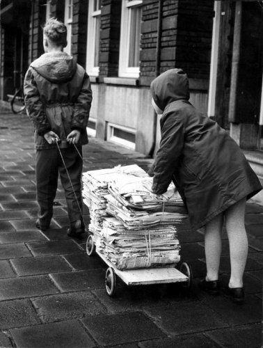 Oude kranten ophalen: twee kinderen op straat in een regenachtige stad met een karretje met oude kranten die ze kunnen verkopen bij de oud papier handel.