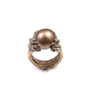Bague perle marron entre les mains d'un squelette en or et diamants bronze