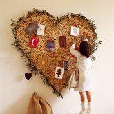 Panneau mural en forme de coeur avec bouchons de liège et feuilles d'olivier.