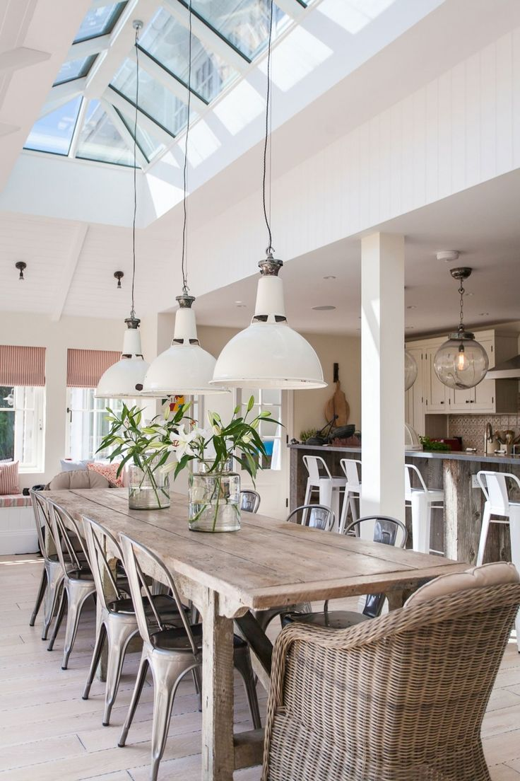 Rattan chairs. Dining chairs and low modern industrial style lighting | love how the skylight brightens up the room