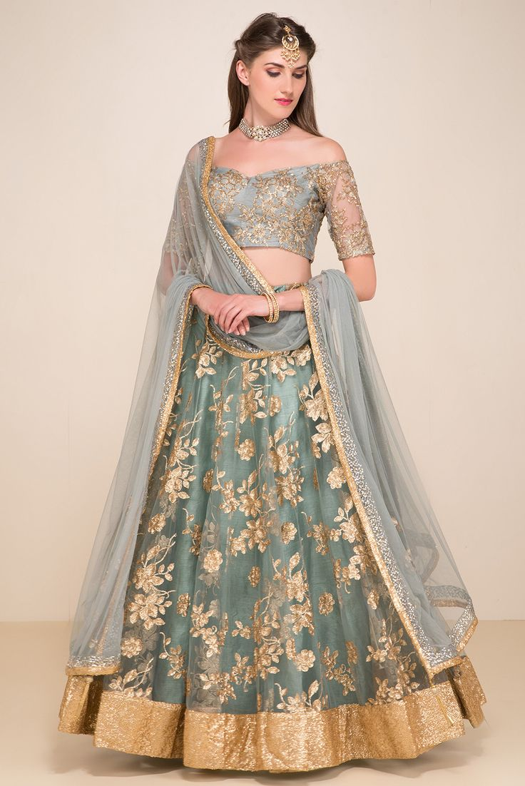 The bardot neckline blouse is adorned with floral sequin embroidery. It is paired with a net flared embroidered lehenga and net dupatta. gold grey blue silver by 6Y collective lengha