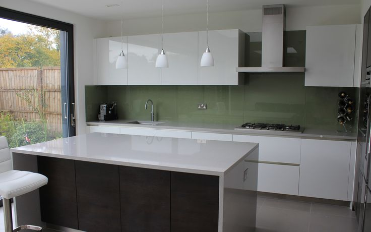 Silestone Aluminio Nube quartz kitchen worktops and island with white cabinets and a contemporary green glass splashback. Installed in Wimbledon, London.