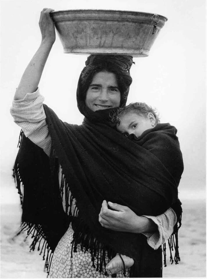 Mamma con scialle, con una secchia in testa e un bimbo in braccio.