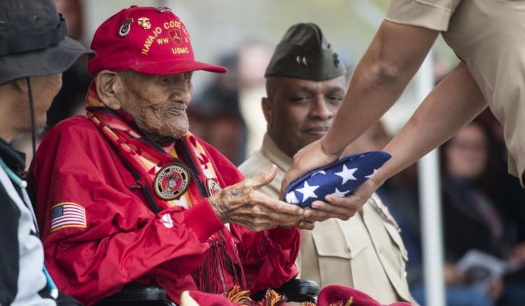 last of the Navajo Code Talkers  U.S. Marine Corps Cpl. Chester Nez receives an American flag from Pfc. Tiffany Boyd, at Code Talker Hall, Marine Corps Base Quantico, Va., April 4, 2014.ing Rededication