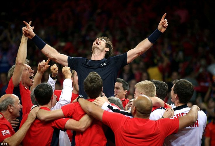 Andy Murray celebrates  and is mobbed by team-mates after helping Great Britain claim a fi...