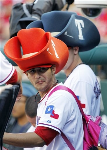 Texas Rangers relief pitchers Martin Perez (33) and Tanner Scheppers (behind Perez) sport oversized foam cowboys hats in the dugout prior to the start of a baseball game against the Chicago Wite Sox on Sunday, July 29, 2012, in Arlington, Texas. (AP Photo/John F. Rhodes)