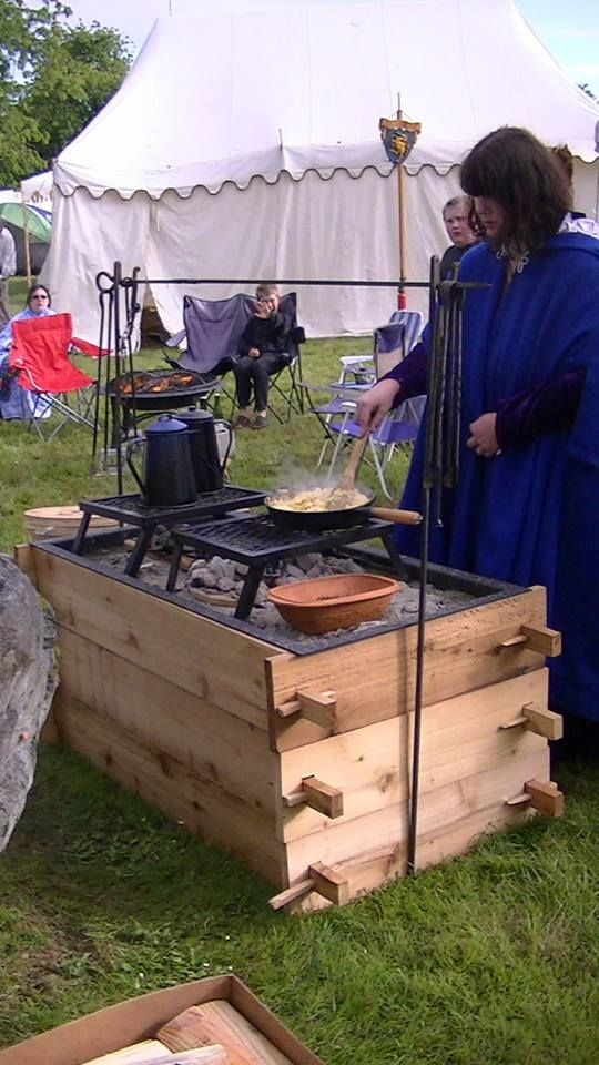 """Great cooking set up - no more bending over the fire. I built this for my wife (seen here using it) in 2013 out of a need for a cooking area. It has since become very popular with the ladies in my household as well as other women. Plans are available from me (Eric Olsen, Clan Chief for Clan Black Stag ) for """"Free""""upon request..."""
