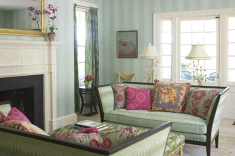 Monochromatic green striped walls, white painted trim, and lots of floral throw pillows shades of sage green and deep pink.