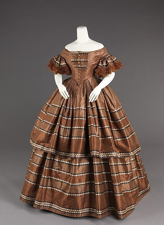 Silk border stripe a` dispositon, American, 1858-59. Pointed low body appears to have functioning front closure, densely gathered sleeve flounces with fringe, 2-flounced skirt triple box pleated at waist. Has the appearance of formerly havng been a high body dress. MET