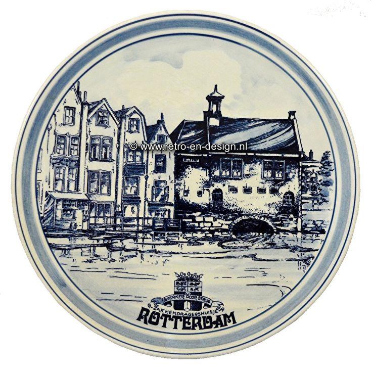"""Wandbord Rotterdam, Zakkendragershuis 'Sterker door strijd'. Delfts handbeschilderd  Handbeschilderd wandbord met afbeelding van het Zakkendragershuis in Rotterdam. Uit serie wandborden """"Sterker door strijd"""".  Delfts handbeschilderd. Genummerd en gesigneerd.  Diameter: 26 cm. zie: http://www.retro-en-design.nl/a-43352085/aardewerk/wandbord-rotterdam-zakkendragershuis-sterker-door-strijd-delfts-handbeschilderd/"""
