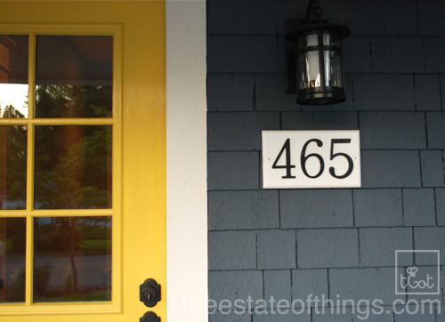 yellow door. blue siding. black house numbers.