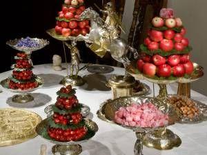 Konfektbordet med den förgyllda tårtan är festens praktfulla final. På vackra silverfat och i skålar finns marsipanfigurer, kanderade blommor, frukter som plommon, körsbär och äpplen, hasselnötter, kastanjer och brända mandlar. En närmare titt på sötsakerna, som kom från sockerbagare i de större städerna, avslöjar bibliska motiv och figurer, gärna överdragna med guld. Våra dagars jultomtar och påskkycklingar i choklad och marsipan är ett arv från dessa figurer. Foto: Mats Landin, Nordiska…
