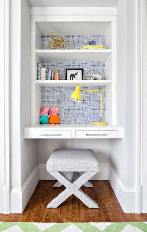 Fabulous kid's room features an alcove filled with a floating desk with two drawers paired with gray x stool under walls clad in denim blue wallpaper lined with stacked shelves illuminated by a yellow task lamp.