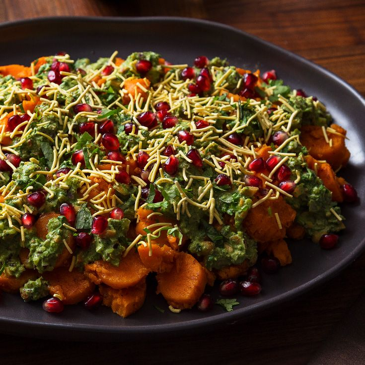 Roasted sweet potatoes are tossed in a mint chutney before getting topped with a bright cilantro sauce in this Indian side dish.