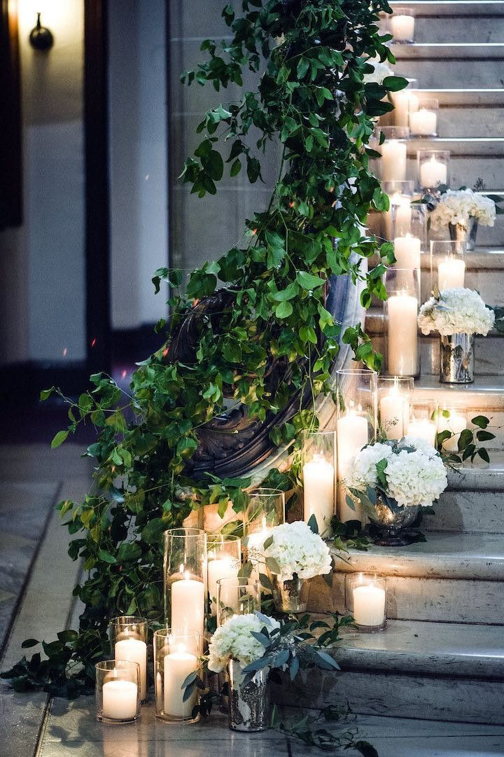 stunning wedding reception entrance; photo: Amanda Miller Photography with foliage on staircase and pillar candles