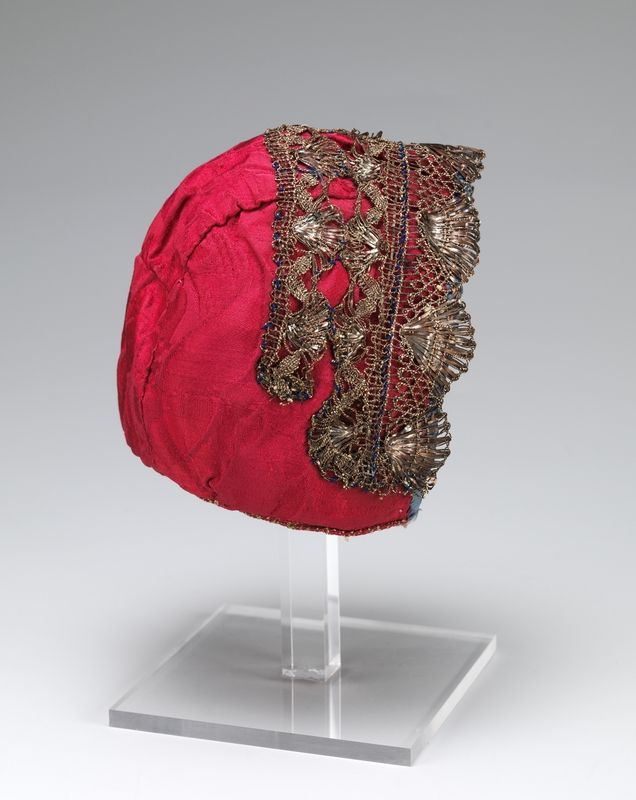 Infant's cap, Norway, 18th century. Red silk damask decorated with silver metallic lace.