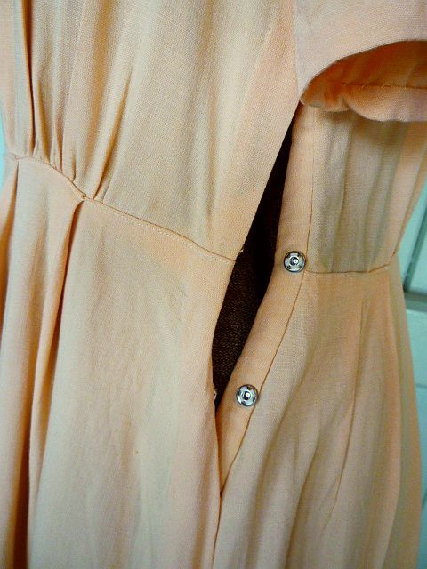 A side opening with metal press snaps. The forties woman would always have left the house wearing proper foundation garments. At the time, that would have meant a super-tight girdle and a full slip over the top. These allowed dresses a neater and better fit and meant that pesky side zip (or worse) was easy to close.