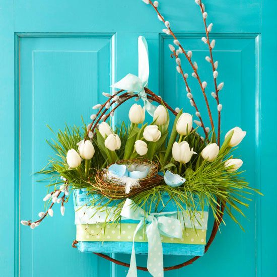 A bright blue wicker basket filled with white tulips is a welcome sign of spring that will complement any door.   Make the Easter Door Decoration: Choose a basket with a flat side so it will lay flat against your door, then fill with white tulips (placed in lightweight cups of water), grass, and a tiny bird's nest filled with cracked eggshells. For a final touch, add a band of ribbon around the bottom of the basket. Tie a pretty bow in front and on top of the handle to hang.