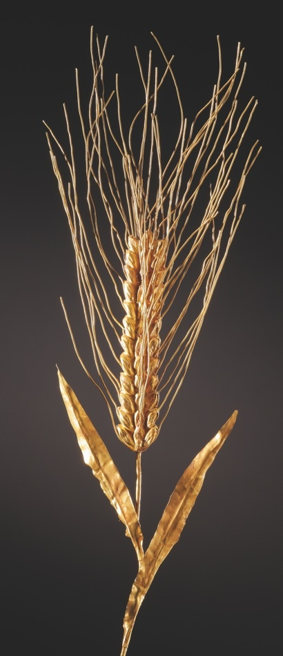 H. 13.8 cm. Gold. Greek, 4rh-3rd cent. B.C. A rare example of an ear of wheat made of gold. Two elongated leaves at the top of the stalk. The ear consists of three rows of kernels. The silk strands that emerge from the kernels are made of fine wire. The silk infront and at the back is pressed close the ear. The leaves show traces of bending.