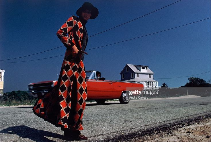 Model, standing on the side of the road with a car and house behind her, wearing a Cuddlecoat ...long gray-and-orange argyle maxi coat over matching arrow-straight pants, by Victor Joris, and a large-brimmed hat.