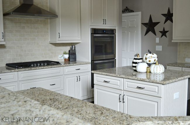 wihte kitchen | neutral kitchen | dream kitchen | subway tile | white grout | neutral granite counter | stainless steel range hood | neutral backsplash | double oven | kitchen island with bead board | gold black white pumpkins | cabinet pull inpsiration | pewter cabinet pulls | cabinet knobs | white cabinets | ivory cabinets