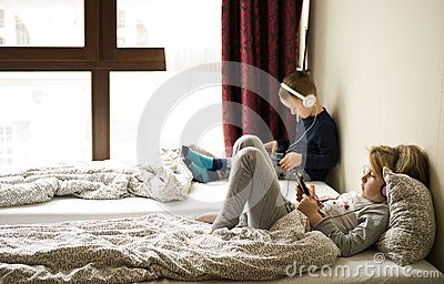 Two children playing in large bedroom bed next to big window, using their mobile devices such as phones and tablets.