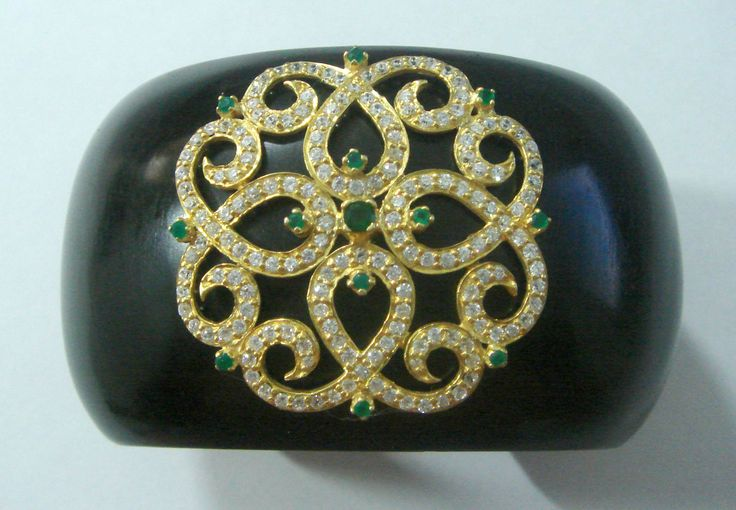 Artisan wood cuff with intricate gold plated silver design studded with high quality cubic zirconia and accented with beautiful emeralds!