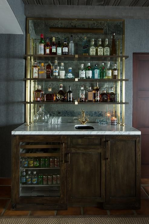 Chic rustic wet bar boasts dark stained oak cabinets fitted with a glass door beverage fridge topped with white marble lined with a bar sink and an antique brass vintage faucet under stacked wood and brass shelves lining an antiqued mirrored backsplash.