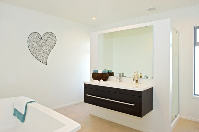 Clever design creates space and privacy in the bathroom. A central wall to separate shower and bath.