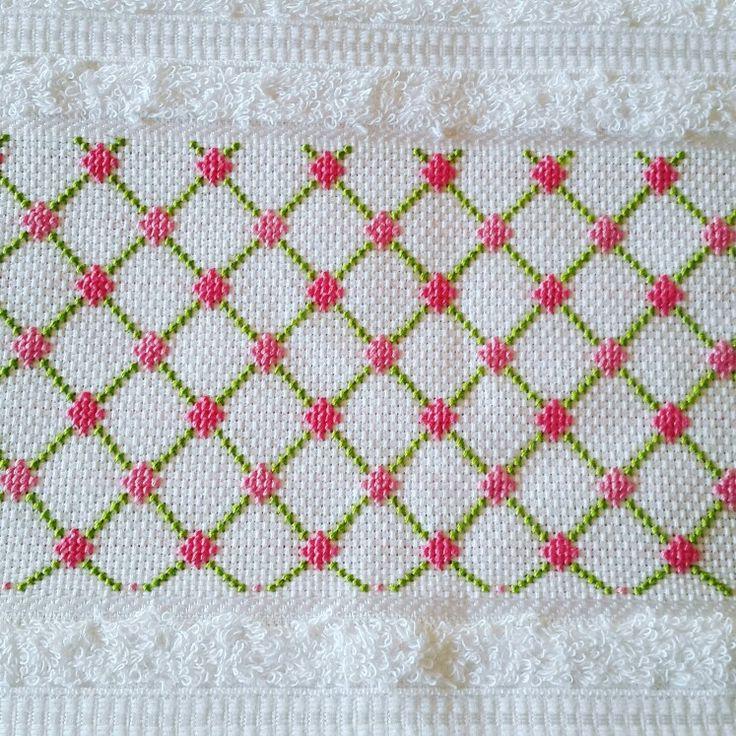 Toalla bordada en punto cruz con figuras geográfica, rosa y verde