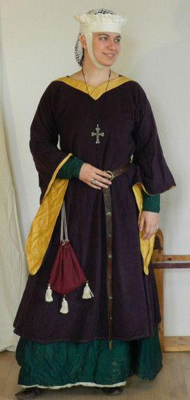 Hochmittelalter Oberkleid aus lilafarbener Wolle. Die Ärmel sind mit goldfarbener Seide gefüttert. Der Kragen ist quadratisch und mit der gleichen Seide besetzt. Alle sichtbaren Nähte sind mit gelbem Leinengarn handgenäht.