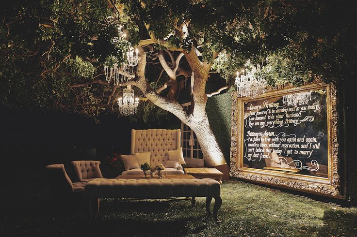 Plush, tufted lounge furniture was situated under a large tree adorned with sparkling crystal chandeliers. A large, gold-framed mirror was painted with quotes from Brittney Palmer and Aaron Zalewski's vow exchange. Photography: Daniel Kincaid Photography Read More: http://www.insideweddings.com/weddings/brittney-palmer-and-aaron-zalewski/595/