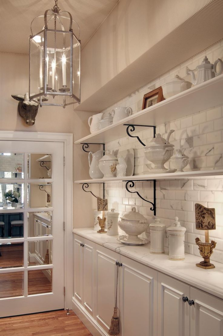 The butler's pantry offers abundant storage between the open shelving and traditional cabinetry. An oversized lantern ensures the beautiful utility room isn't left in the dark.