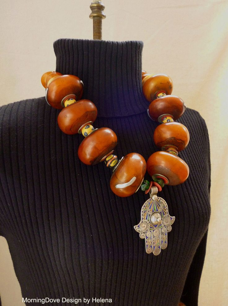 Necklace   Helena Nelson-Reed.  Contemporary North African 'amber' resin beads, antique bone disks, antique African trade beads and contemporary Hand of Fatima/Hamsa from Morocco   Sold